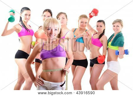 Group of fitness girls holding measuring tape, dumbbells, scales and boxing gloves. Portrait of sport young women with perfect bodies, studio shot over white