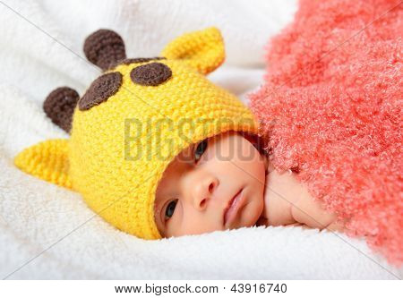 cute baby sleeping in funny  hat and smiling in sweet dreams, beautiful kid's face closeup