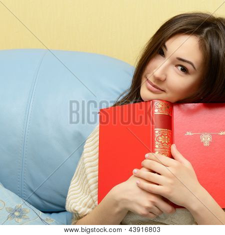 cheerful attractive teenager girl reading book on sofa at home