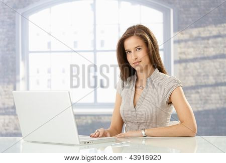 Attractive woman sitting at table with laptop computer, looking at camera.