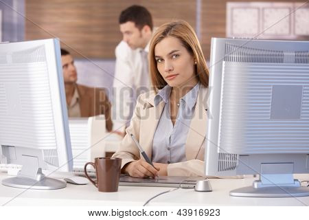 Young woman learning computer graphic design at further education.
