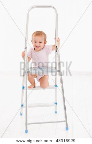 Adorable baby girl in bodysuit climbing on ladder, smiling.