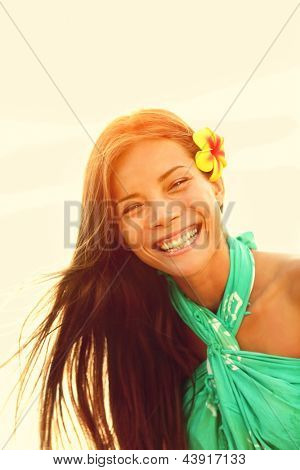 Sunshine smiling summer girl laughing happy looking at camera enjoying the summer sun sunset during holidays vacation. Young woman on Hawaiian beach. Pretty multicultural Asian Caucasian female model