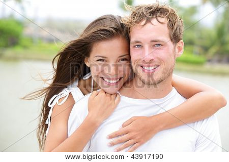 Young couple smiling happy portrait outdoors. Interracial couple in love together outside looking fresh and joyful at camera. Asian woman, Caucasian man.