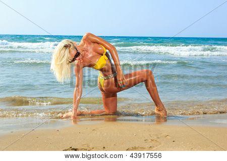 Beautiful young blonde fit woman in bikini on the beach