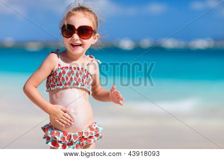 Adorable little girl at tropical beach applying sunblock cream