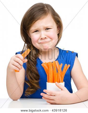 Cute little girl is eating carrot and feel very unhappy about it, isolated over white