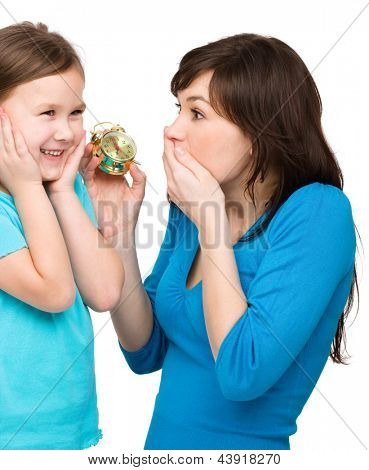 Little girl and her mother are anxious about time, isolated over white