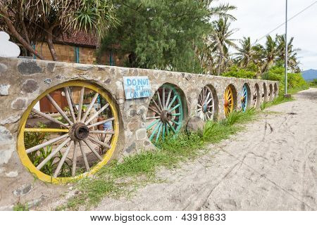 Wall designed with wooden cartwheels painted in yellow and green