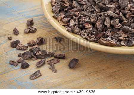 Raw cacao nibs in a small ceramic bowl against grunge wooden background