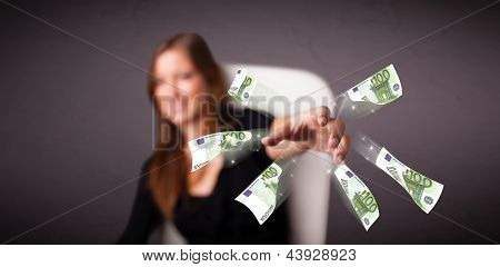 Pretty young woman sitting and throwing money