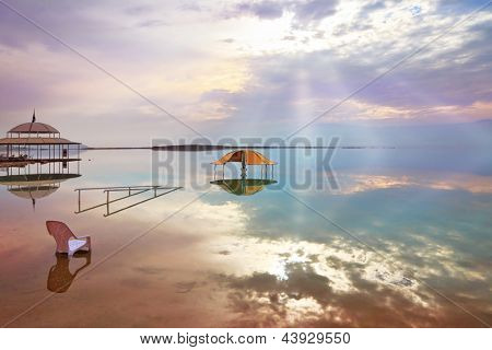 A stunning visual effect on the Dead Sea. The picturesque gazebo for bathers and sun rays are reflected in a smooth sea surface.