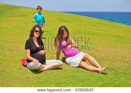 Zwei junge schwangere Frau in Sonnenbrille posiert auf dem Gras-Rasen. Junge Sohn eines von ihnen kommt t