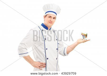 Male chef holding a small shopping cart with food products, isolated on white background