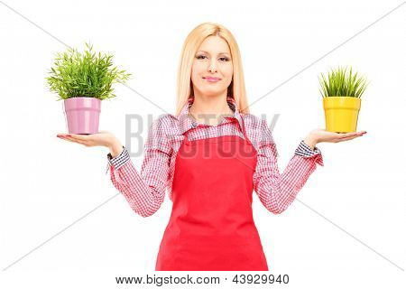 A blond female gardener holding two potted plants isolated on white background