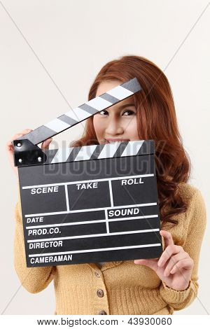 woman hiding behind the film slate