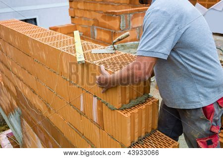 anonymous construction worker at a building site built in house-building, a wall of bricks. brick wall of a solid house. icon image for undeclared work and bungling