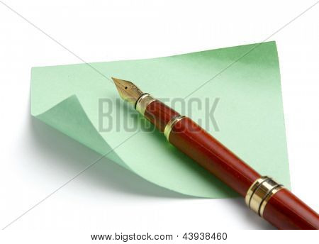 Pen and green note paper, isolated on white background