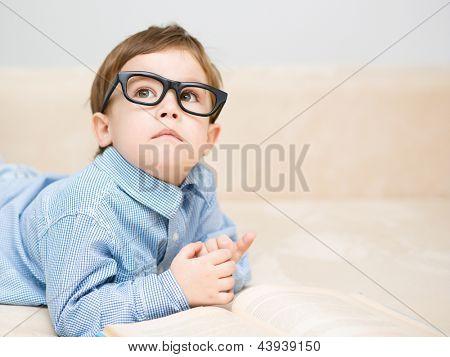 Niño está leyendo libro sentado en el sofá, sesión de interior