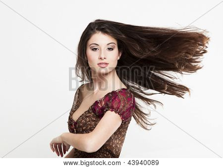 Portrait of a beautiful and atractive fashion woman with moving hair, isolated on white