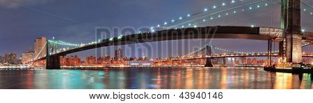 New York City Manhattan Bridge and Brooklyn Bridge with downtown skyline panorama over East River at night
