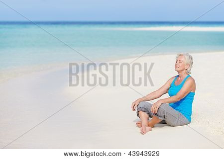 Sênior mulher meditando na bela praia de