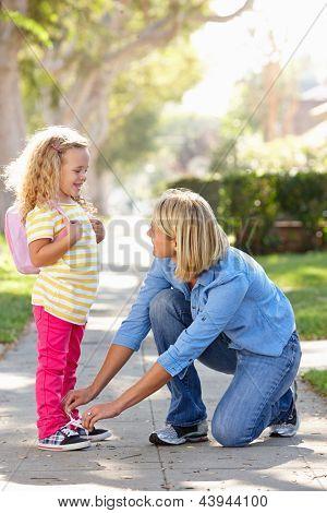 Madre hija de ayudar a atar cordones de los zapatos en camino a la escuela