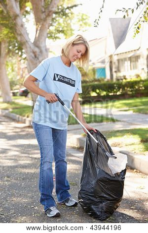 Woman Picking Up Litter In Suburban Street