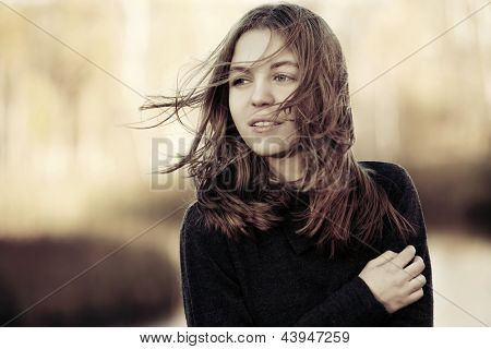Young girl in the wind against a nature background
