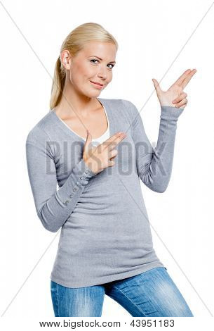 Girl in gray sweater gesturing guns with her hands, isolated on white