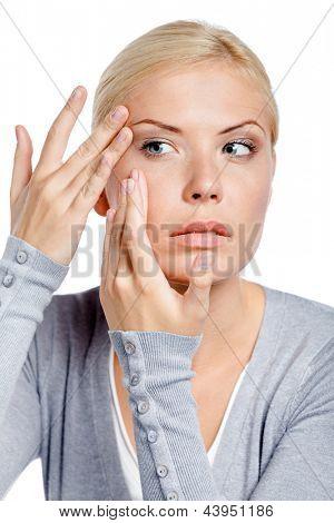 Joven, examinando su cara y las arrugas que pueden aparecer, aislado en blanco