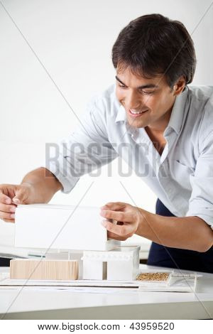 Young male architect preparing a model house on desk