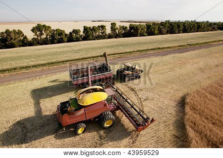 Large combine unloading seed into a grain cart on a prairie field