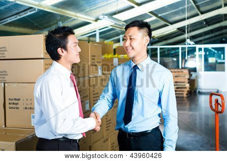 Manager, owner or businessmen in a warehouse of a forwarding agency or a factory shake hands