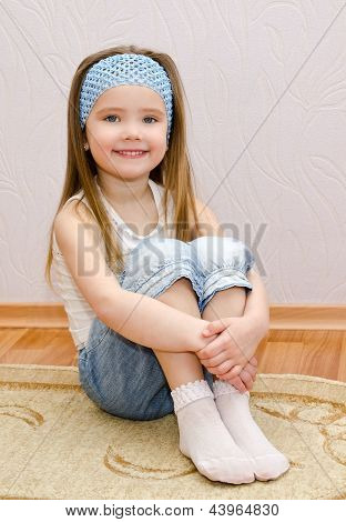 Smiling Little Girl Sitting On A House Floor