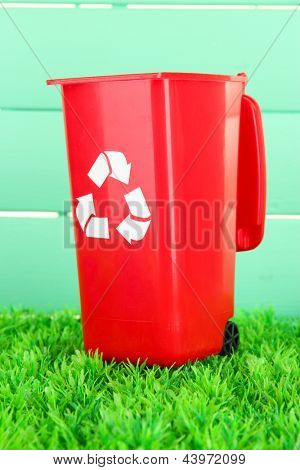 Recycling bin on grass on light blue background