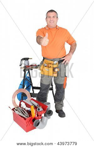 55 years old handyman doing thumbs up surrounded by a lot of tools and materials