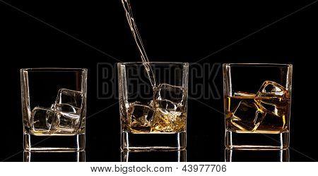 Whiskey glasses with splash, isolated on black background