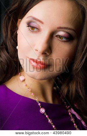 face of beautiful brunette girl in purple dree