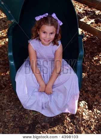 Young Girl Sitting On A Slide