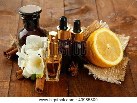 Bottles with ingredients for the perfume on wooden background