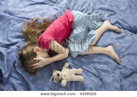 Little Sad Crying Girl Lying On The Bed