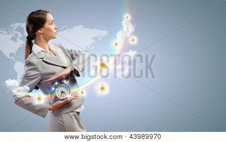 Imagen de la joven empresaria sosteniendo alarmclock contra el fondo de la ilustración