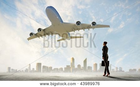 Image of business woman holding suitcase looking at airplane in sky
