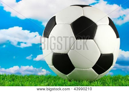 football ball on green grass, on blue sky background