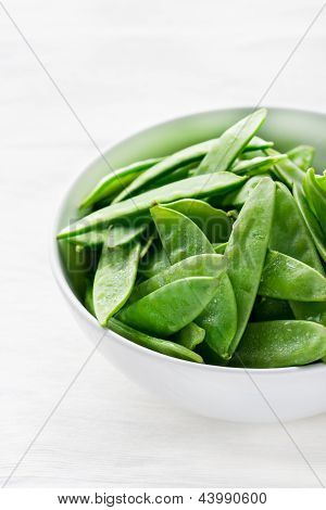 Snow peas in white bowl light