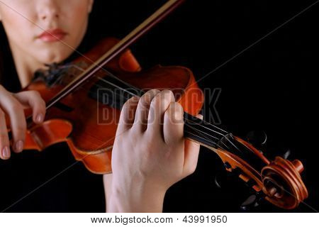 Musician playing violin on black background
