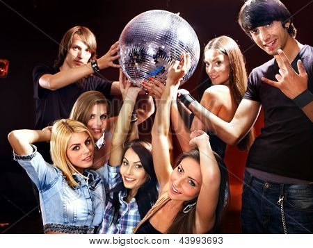Group people on disco in night club. Lighting effects.