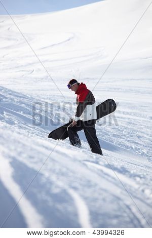 Snowboarder walking up a mountainside