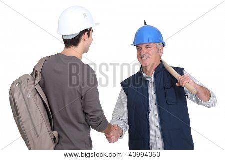 Builder welcoming teenage helper